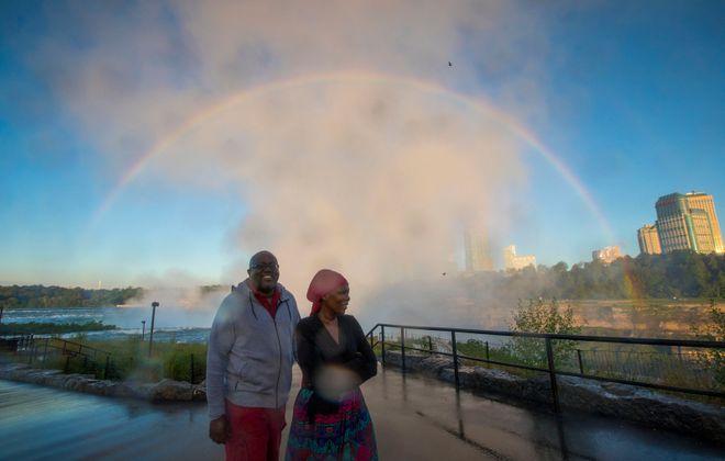 James and Sta Maodzwa, visitors from Zimbabwe, with Niagara Falls at dawn. (Derek Gee/The Buffalo News)