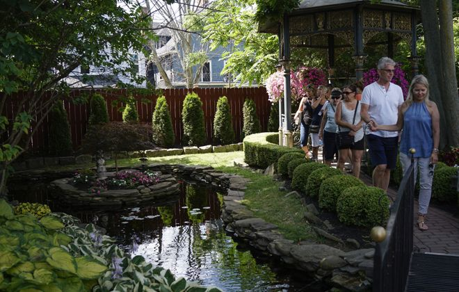 Visitors take in a garden on Norwood Avenue on July 29 during Garden Walk Buffalo. The  Association of Garden Communicators will tour some local gardens, as well as parks and public gardens, on  Aug. 5-7 during the organization's annual conference taking place in Buffalo. (Derek Gee/Buffalo News)