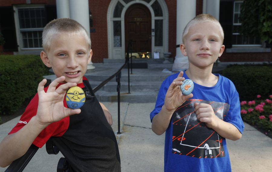 Kristina Gassman's sons, Wyatt, 8, left,  and Landin, 7, have been shuttled between relatives and just a couple of days ago came to stay with their mom at the Ronald McDonald House. They walked outside on their way to the hospital when they found two painted rocks -- a minion and a fish and declared them good luck rocks for their sister. (John Hickey/Buffalo News)
