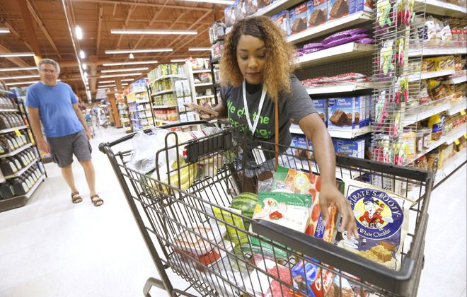 Professional shopper Brianna Johnson of Buffalo uses her smartphone and the app to shop and scan for a customer's order at the Wegmans location on Alberta Drive in Amherst in 2017.  (Robert Kirkham/News file photo)