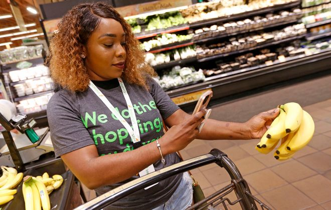 Professional shopper Brianna Johnson of Buffalo uses her smartphone and the Instacart app to shop for a customer's order at the Wegmans on Alberta Drive in Amherst. Today is the first day that people can order groceries at Wegmans and have them delivered by third-party company Instacart. (Robert Kirkham/Buffalo News)