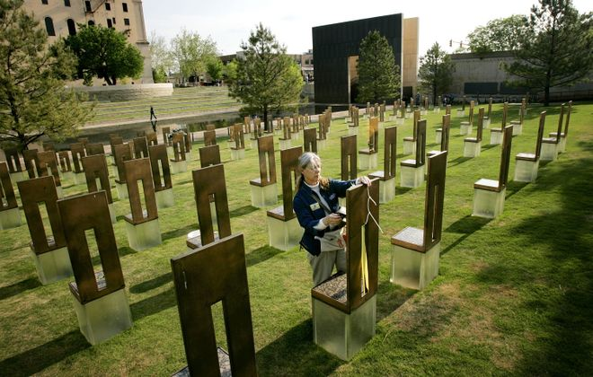A volunteer at the Oklahoma City National Memorial tends to one of the chairs representing the 168 people killed in the 1995 bombing of the Alfred P. Murrah Federal Building in 1995. At the time, it was the worst domestic terror attack in U.S. history. (Photo by Win McNamee/Getty Images)