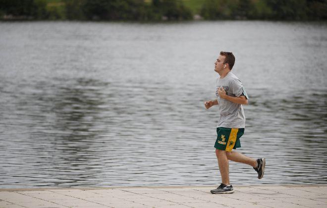 A jogger runs alongside Hoyt Lake in Delaware Park. (Sharon Cantillon/Buffalo News)