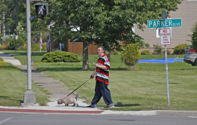 A man walks his dog at the intersection of  Decatur Street and Parker Boulevard near Lincoln Park in the Town of Tonawanda on Tuesday, Aug. 1, 2017. The town is considering changes to the traffic flow on Parker Boulevard, with new bike lanes, roundabouts, and narrower lanes for cars to slow traffic on the busy road. (Robert Kirkham/Buffalo News)
