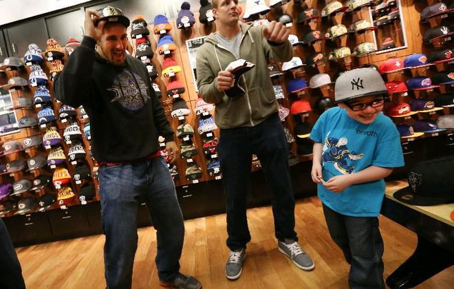 New Era Cap treated nine children from Carly's Club to new caps in March 2015. New England Patriots star Rob Gronkowski, center, and his friend WWE wrestler Mojo Rawley, left, try to get Luke Gworek, of Grand Island, to dance.  (Sharon Cantillon/Buffalo News)