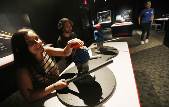 Miquela Chudy of Fredonia and Matt Walker of Buffalo fire paper air rockets at the launching station in the new space exhibit during a visit to the Buffalo Museum of Science. (Derek Gee/Buffalo News)