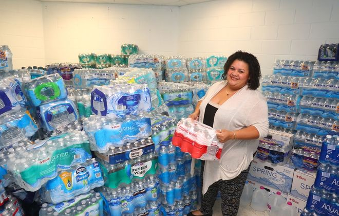 Lizbeth Medina  looks over the bottled water donated for Puerto Rico. The Father Belle Center is one of several centers that will be accepting donations through Oct. 6. (John Hickey/Buffalo News)