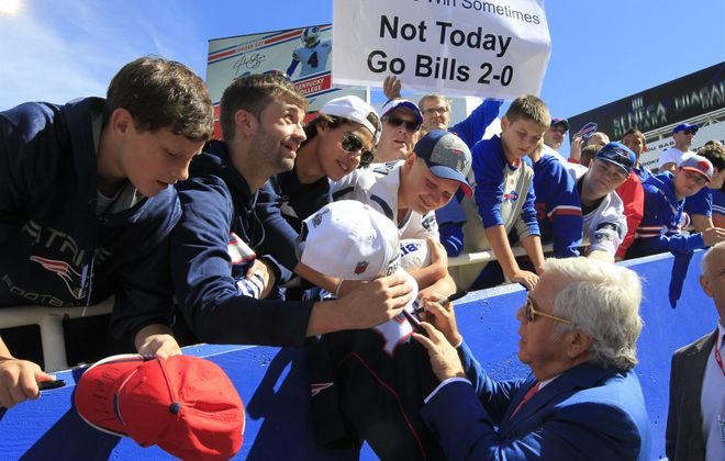 A Bills fan holds an anti-Patriots sign at a 2015 game while Patriots owner Robert Kraft signs autographs. (Harry Scull Jr./Buffalo News)