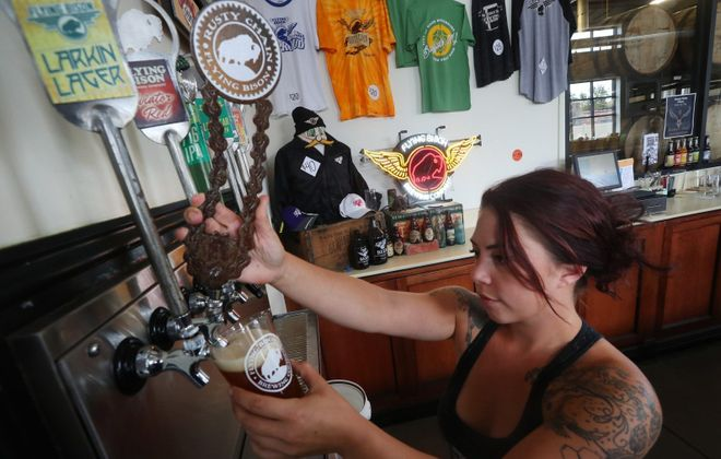 Bartender Siobhan Melynk pours a Rusty Chain draft at Flying Bison, among the nearly 30 Western New York breweries gearing up for Buffalo Beer Week, which starts Sept. 22. (John Hickey/Buffalo News)
