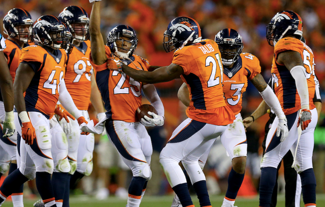 Broncos DBs Chris Harris (finger raised) celebrates an interception. (Getty Images)