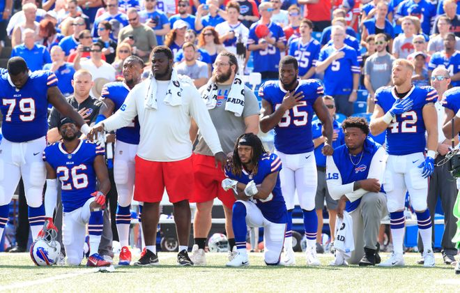 Buffalo Bills players stand and kneel during the national anthem prior to a 2017 game against the Denver Broncos. (Harry Scull Jr./ News file photo)