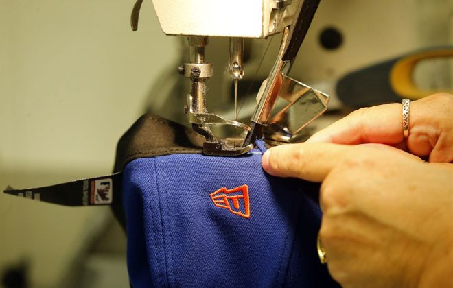 The sweatband is sewn to the inside of the hat by Flex team member Sharon Sager at the New Era factory in Derby. (Mark Mulville/Buffalo News)