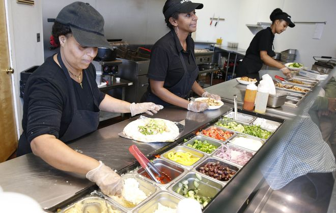 Meaza Tedela, left, and manager Metsie Worku fill customer orders at the former Rachel's Mediterranean on Delaware Avenue that moved to Elmwood Avenue and West Chippewa Street. (Sharon Cantillon/News file photo)
