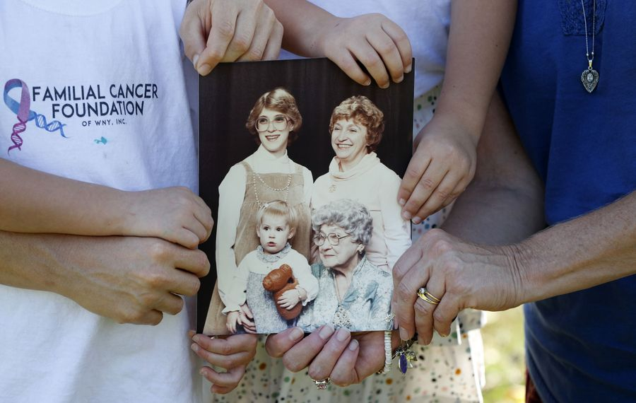 Andrea Whitmarsh, her daughters and her mother, Dawn Sagerman, hold a copy of a photo of, from top left, Sagerman, Sagerman's mother, Shirley Maggio, her grandmother, Julia Maier, and her oldest daughter, Erica Desaulniers. Sagerman was pregnant with Whitmarsh when the photo was taken. Whitmarsh and Sagerman learned they have the BRCA2 gene mutation after Maggio and Maier died of breast cancer. Desaulniers tested negative for the mutation. All three women have become involved with the new Familial Cancer Foundation of Western New York. (Mark Mulville/Buffalo News)