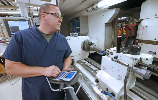 Patrick Barrett, of North Buffalo, a machinist, works on a part for an aircraft steering system at Moog's Elma plant. Barrett is one of the youngest employees at the motion control company, which is preparing for a wave of retirements in coming years. (Robert Kirkham/Buffalo News file photo)