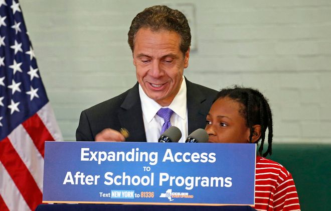 "Gov. Andrew M. Cuomo hands his New York State lapel pin as a prize to Tyree Scott, a third-grader, who guessed the magic word, ""love,"" that officials say motivated the state's new ""Expanding Access to After School Programs."" Cuomo spoke at an assembly at Hamlin Park School in Buffalo on Nov. 16. (Robert Kirkham/Buffalo News)"