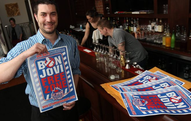 "Anthony Lynch hangs a ""Bon Jovi Free Zone"" poster at Savoy on Elmwood Avenue in Buffalo on May 21, 2014. (Sharon Cantillon/News file photo)"