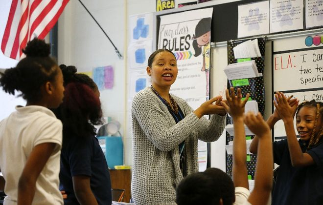 Fourth-grade teacher Tiffany Bryant works with students on a science lesson at BUILD Academy, where the principal expects improved tests cores this year even as the school faces a state takeover. (Mark Mulville/Buffalo News)