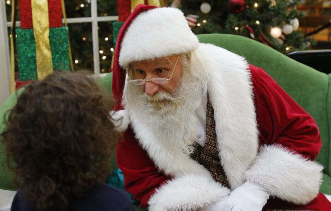 Santa Claus (aka Mike Stroh) listens closely as a curious 4-year-old Tristen Goldring asks a question at the Walden Galleria Mall in this 2014 photo. Kids can meet Mr. Claus at the revived Santa Village in the Town of Tonawanda later this year.  (Derek Gee/Buffalo News file photo)