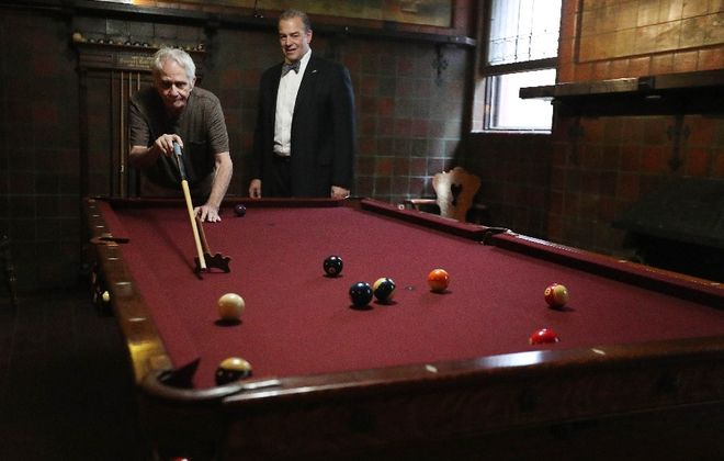 Danny DiLiberto, 1972 national billiards champion and Greater Buffalo Sports Hall of Fame inductee, tries out the 1890s era pool table that made its way to the Victorian-era InnBuffalo off Elmwood as co-owner Joseph Lettieri looks on. (Sharon Cantillon/Buffalo News)
