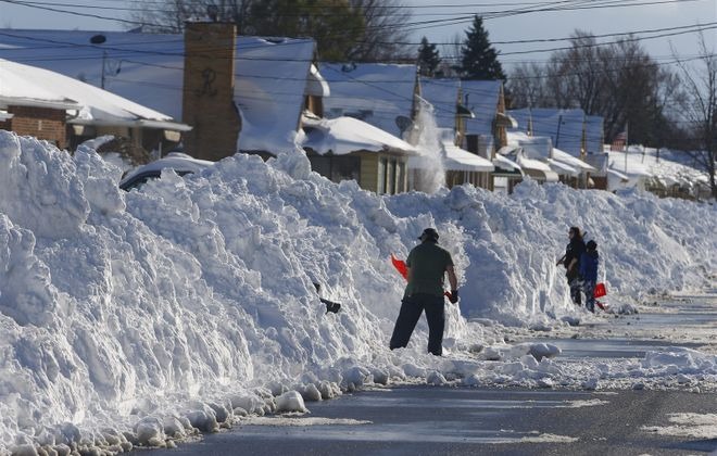 Residents dig out to the street on Collins Road in West Seneca on Friday November 21, 2014. (John Hickey/Buffalo News)
