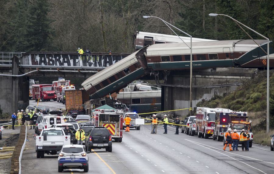 Emergency crews work at the scene of an Amtrak train derailment on Dec. 18, 2017, in DuPont, Wash. At least three people were killed when a passenger train car plunged from the bridge. The derailment also closed southbound I-5.  (Photo by Stephen Brashear/Getty Images)