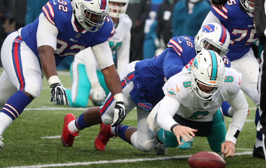 Miami Dolphins quarterback Jay Cutler (6) fumbles while tackled by Buffalo Bills defensive end Ryan Davis (56) in the fourth quarter at New Era Field on Sunday, Dec. 17, 2017. Cap Capi (75) is seen at right. (James P. McCoy/Buffalo News)