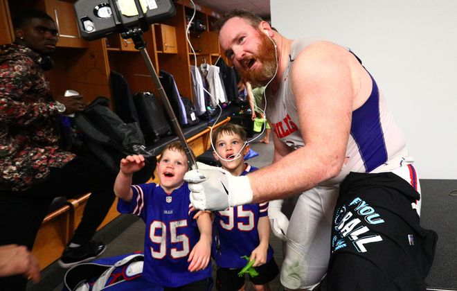 Buffalo Bills defensive tackle Kyle Williams (95) makes calls from the locker room with his kids after his team made the playoffs for the first time in 17 years. (James P. McCoy / Buffalo News)