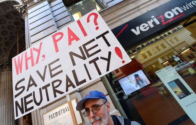 A small group of protesters supporting net neutrality protest against a plan by Federal Communications Commission head Ajit Pai, during a protest outside a Verizon store on Dec. 7 in Los Angeles. ( ROBYN BECK/AFP/Getty Images)