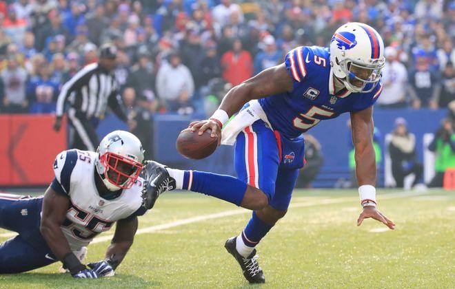 Buffalo Bills quarterback Tyrod Taylor gets tripped up by New England Patriots' Eric Lee. (Harry Scull Jr./Buffalo News)