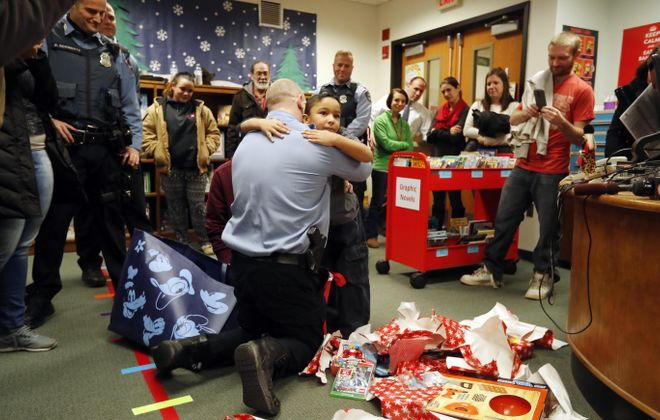 Emetrious Harless, 6,  hugs Cheektowaga Police Sgt. Caleb Harte after opening Christmas presents he received from the Blue Mittens Project at Union East Elementary School in Cheektowaga on Wednesday, Dec. 20, 2017.  (Mark Mulville/Buffalo News)