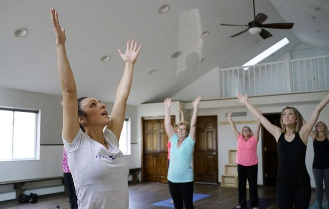 Teresa DeLabio left, leads a Holy Yoga class at The Fountain Wellness Center in Clarence. The practice blends traditional yoga poses with Christian music and prayer. (Derek Gee/News file photo)