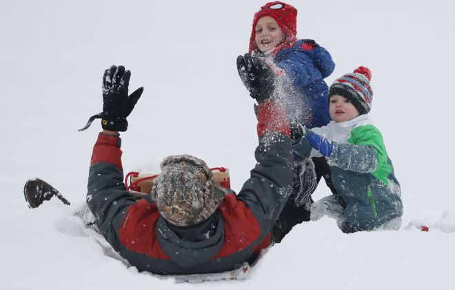 Tim Kawalerski, left, of Alden, gets a high five from his son Alex, 5, at the end of a toboggan ride at Chestnut Ridge. On right is Paul Dombrowski, 3.  (Sharon Cantillon/Buffalo News)