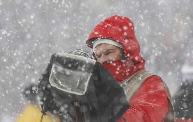 Buffalo News photographer James P.  McCoy works through the snow (Timothy T. Ludwig/USA TODAY Sports)