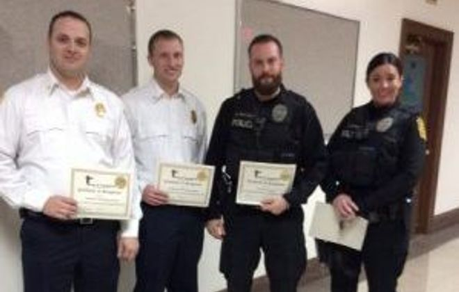 The Town of Tonawanda recognized more than a dozen people for their work rescuing two people from a burning building on Glenside Avenue. Among those recognized are, from left, Brighton Fire Chief Andy Hallnan, 2nd Chief Steve Dabney and Town of Tonawanda officers Mark Muscoreil and Kelly Wright.