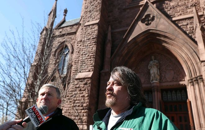 Michael Whalen, right, speaks in front of St. Louis Roman Catholic Church about being sexually abused as a child by the Rev. Norbert Orsolitis. In light of this and other reports, the church should re-evaluate policies on requiring celibacy and prohibiting women priests. (Sharon Cantillon/Buffalo News)