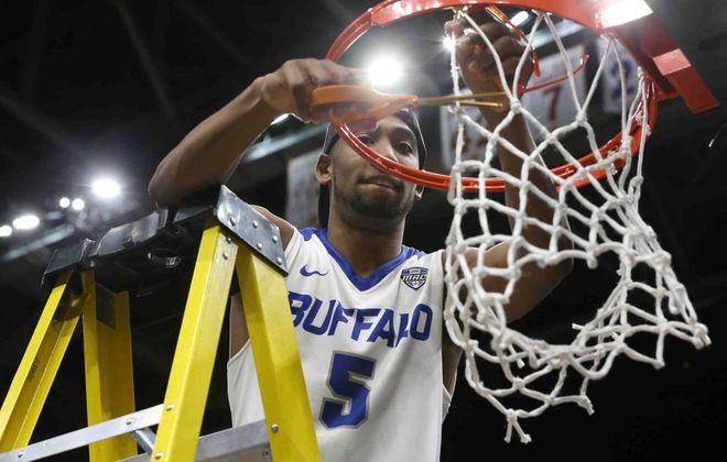 Buffalo Bulls guard CJ Massinburg (5) cuts down the net after beating the Toledo Rockets 76-66 to win the MAC Championship game. (James P. McCoy/Buffalo News)