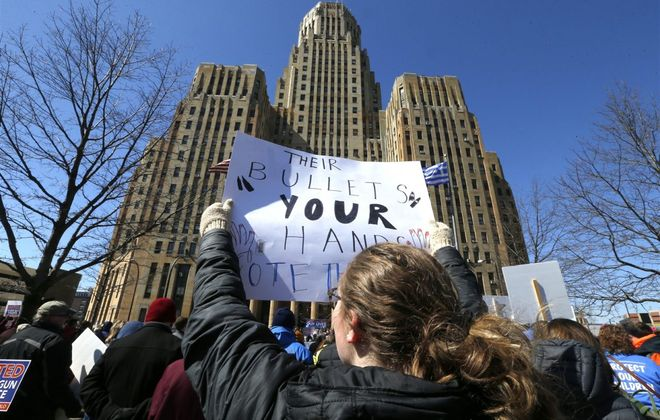 A protester holds a sign on March 24, 2018 in Niagara Square. (Robert  Kirkham/Buffalo News)