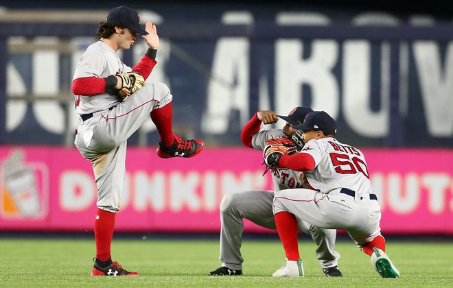 The Red Sox can lay claim to the best all-around outfield in baseball with Mookie Betts (50), Andrew Benintendi (16) and Jackie Bradley Jr. (19). Here they're celebrating a 2017 win at Yankee Stadium. (Getty Images)