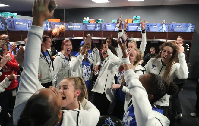 The University at Buffalo women's basketball team celebrates the announcement that it will play in the NCAA tournament. (James P. McCoy/Buffalo News)