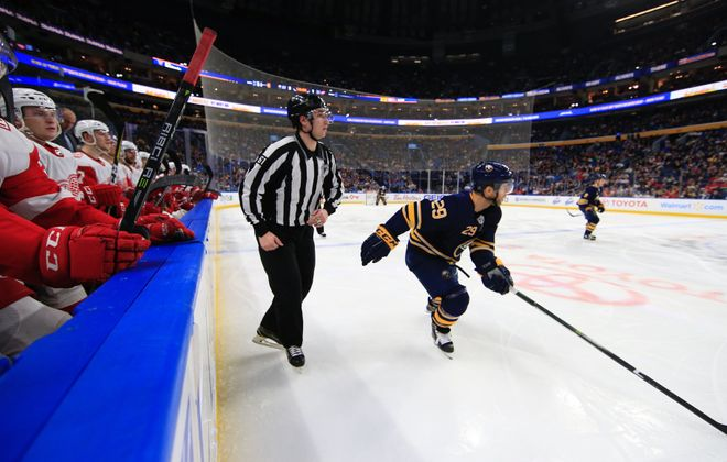 The Sabres' Jason Pominville skates in front of the Red Wings' bench and linesman James Tobias, a graduate of West Seneca West. (Harry Scull Jr./Buffalo News)