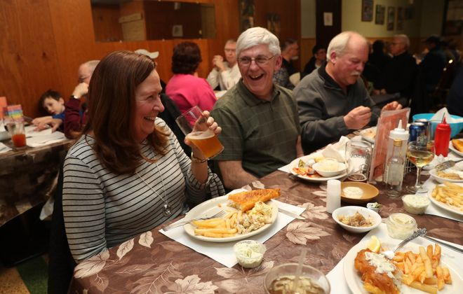 Kathy and Tom Bacon, and Nick Arki, right, sit on one side of the table of a group of lifelong friends, enjoying a fish fry at Eldredge Bicycle Club.  (Sharon Cantillon/Buffalo News)