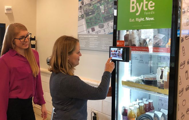 "Farmers & Artisans Market owner Julie Blackman, right, under the watchful eye of Elizabeth Machnica, stocks the new Byte healthy food vending machine, the first of its brand in the region. She calls it ""an exciting next level of farm-to-table."" (Sarah Warner/Special to the News)"
