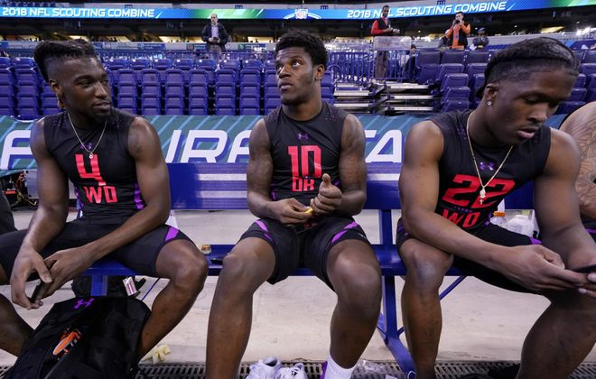 Louisville quarterback Lamar Jackson looks on while talking to Clemson wide receivers Deon Cain (left) and Ray-Ray McCloud (right) during the NFL Combine at Lucas Oil Stadium on March 3, 2018, in Indianapolis. (Joe Robbins/Getty Images)