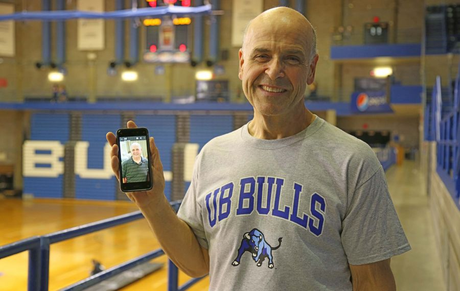 University at Buffalo mail deliverer Michael May holds a photo of what he looked like before his first UB Step Challenge two years and 90 pounds ago. (Yiwen Gu/Special to The News)