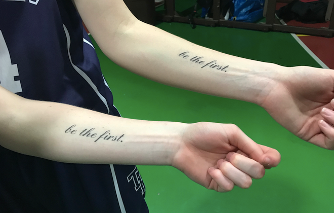"Danielle, foreground, and Allyson Haskell show off their team's temporary ""be the first."" tattoos."