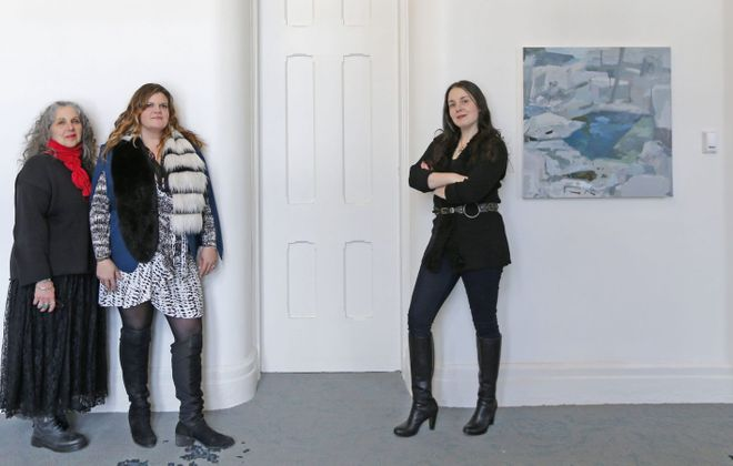 Curators Elisabeth Samuels, left, Emily Tucker and Anna Kaplan launched a collaboration with Hotel Henry last year. They are pictured in one of the hotel's grand corridors with work by Bronx-based artist Rebecca Allan. (Robert Kirkham/Buffalo News)