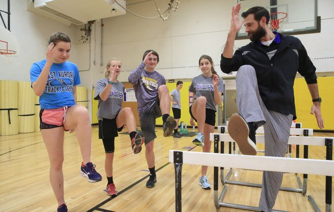 Holland Athletic Director and Holland/East Aurora girls track and field head coach Matt Adams, right, goes over technique with  Eva Scarpa, Kalei Winter, Gunnar Clothier and Laya Davis at Holland Elementary School. (Harry Scull Jr./ Buffalo News)