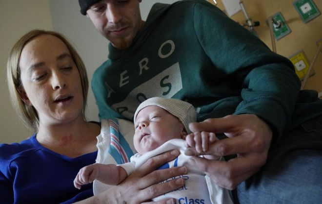 Christopher Everts and Jessica Nydahl holds their 10-week-old son Jaxsyn Everts, who was the first baby to be born at the new Oishei Children's Hospital when it opened on Nov. 10, 2017. Jaxsyn, who was just 2 1/2 pounds when he was born, weighs nearly 8 pounds now as the family prepares to bring him home from the hospital this weekend.  (Derek Gee/Buffalo News)
