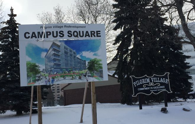 Signs for the new Campus Square project and the existing Pilgrim Village stand in the snow at the inactive project site. (Karen Robinson/The Buffalo News)
